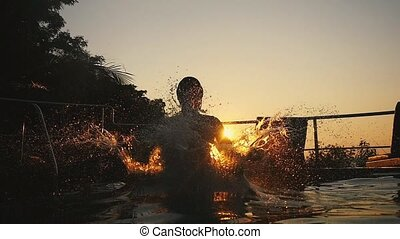 Silhouette of young man jumps in swimming pool water at Sunset through the sun durting beautiful sunset. slow motion. 1920x1080