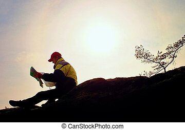 Silhouette of young man looking at a map in nature while hiking