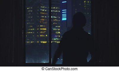 Silhouette of young man opens curtains and admires view from window at home at night. 4k,
