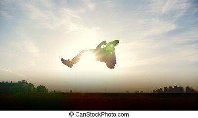 Silhouette of young man outdoors doing acrobatic elements,...
