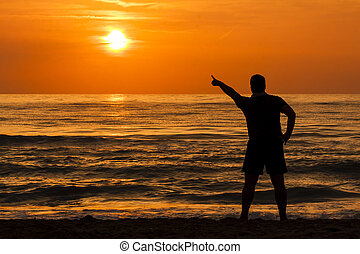 Silhouette of young man pointing out the sun at dawn at sea