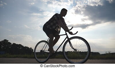 Silhouette of young man riding at vintage bicycle with beautiful sunset sky at background. Guy cycling in the country road. Male cyclist riding fixed gear bike. Healthy active lifestyle Slow motion