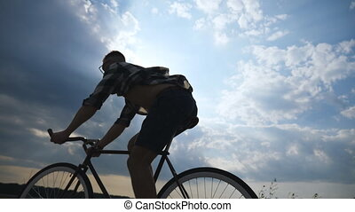 Silhouette of young man riding at vintage bicycle with...