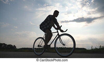 Silhouette of young man riding at vintage bicycle with beautiful sunset sky at background. Sporty guy cycling in the country road. Male cyclist riding fixed gear bike. Healthy active lifestyle Closeup
