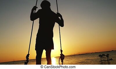 Silhouette of young man swinging on a swing at sunset on the beach. slow motion.