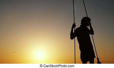 Silhouette of young man swinging on a swing at sunset through the sun on the beach. slow motion. 1920x1080