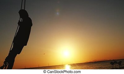 Silhouette of young man swinging on a swing through the sun at beautiful sunset on the beach. slow motion.