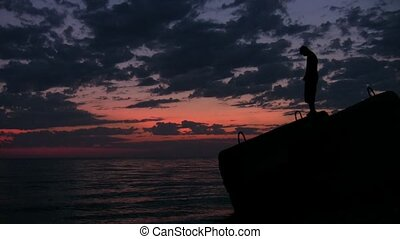 young man walks on flagstone above sunset sea