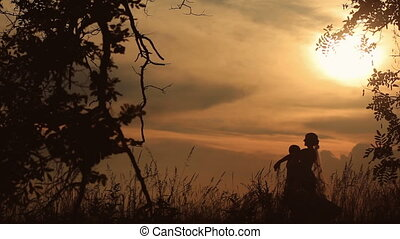 Silhouette of Young Married Couple Dancing In The Field On The Background Of a Sunset