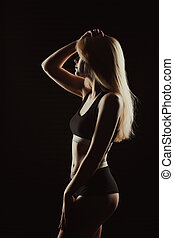 Silhouette of young pretty lady in black underwear the shadow