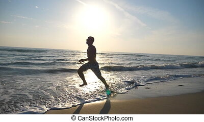 Silhouette of young sporty man running fast along sea shore during sunrise. Athletic boy training barefoot on the beach. Guy stepping in shallow water. Healthy active lifestyle. Slow motion Side view