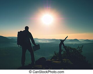 Silhouette of young tourist guide looking in paper map
