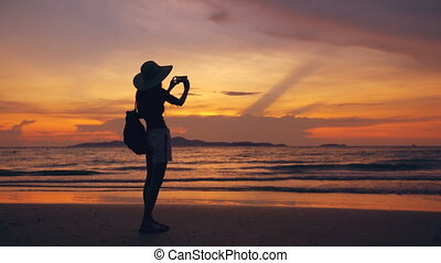 Silhouette of young tourist woman in hat taking photo with cellphone during sunset in ocean beach