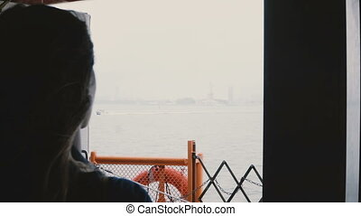 Silhouette of young tourist woman on boat trip to Statue of Liberty, New York taking photos with a camera on cold day.