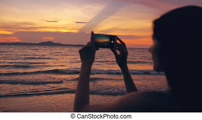 Silhouette of young tourist woman photographs ocean view with smartphone during sunset at beach