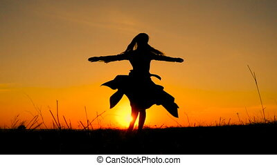 Silhouette of young witch dancing at field against orange...