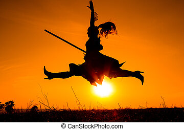 Silhouette of young witch juming with the broomstick