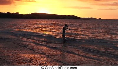 Silhouette of young woman casting rod fishing from the beach...