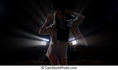 Silhouette of young woman dancing in car lights