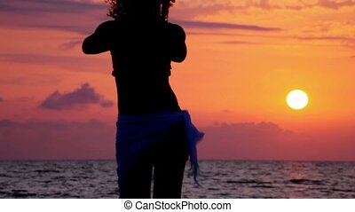 silhouette of young woman dancing on beach, sunset sea and sky in background