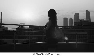 Silhouette of young woman dancing on sunset
