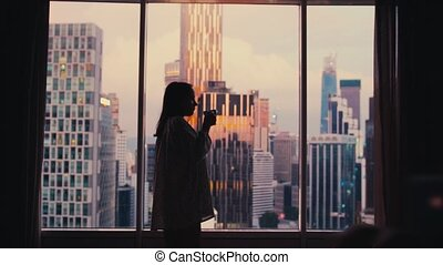 Silhouette of young woman drinks coffee by the window with amazing cityscape view during sunset. slow motion. 3840x2160