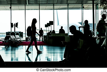 Silhouette of young woman going in waiting hall.