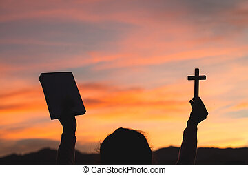Silhouette of Young woman hands holding holy Bible and lift of christian cross, religion symbol in light and landscape over a sunrise, background, religious, faith concept