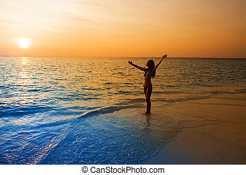 Silhouette of young woman in ocean towards sunset.