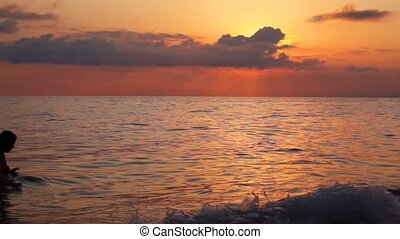silhouette of young woman in sea under sunset sky with clouds