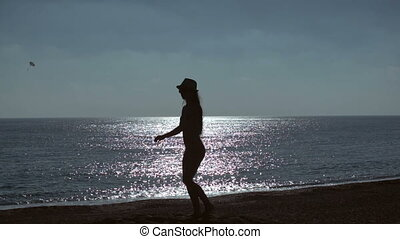 silhouette of young woman jumping on beach on sea background. slow motion