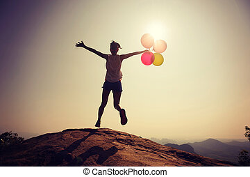 Silhouette of young woman jumping on mountain top with balloons