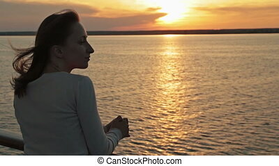 Silhouette of young woman on cruise ship at sunset