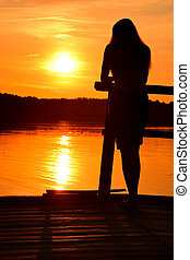 Silhouette of young woman over sunset sky and lake