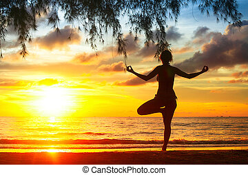 Silhouette of young woman practicing yoga on the beach at sunset.