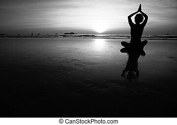 Silhouette of young woman practicing yoga on the sea beach. Black and white high contrast photography.