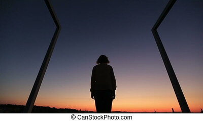 Silhouette of young woman raising up hands to the sky on sunset. Modern high-tech bridge on background