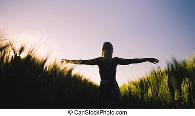 Silhouette of young woman running along wheat field imitates flying bird wings. Sunset flares come up through the wheat