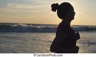 Silhouette of young woman running on sea beach at sunset. Girl jogging along ocean shore during sunrise. Female sportsman exercising outdoor. Healthy active workout lifestyle at nature. Close up