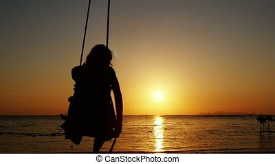 Silhouette of young woman swinging on a swing through the sun at beautiful sunset on tropical beach. slow motion.