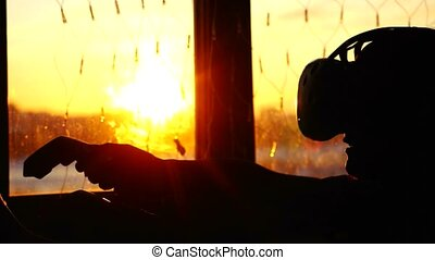 Silhouette of young woman uses a virtual reality glasses at home during sunset with city background from the window and beautiful lense flare effects. 3840x2160 4k