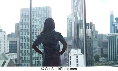 Silhouette of young woman walking and admire city view from...