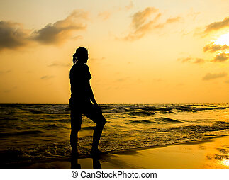 silhouette of young woman walking on beach