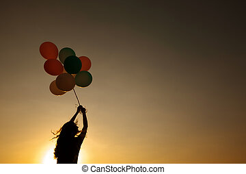silhouette of young woman with flying balloons against the sky.