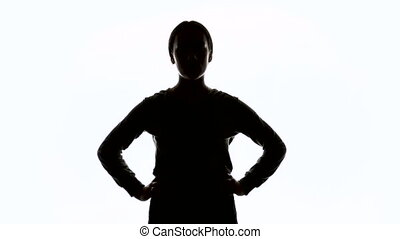 Silhouette of young woman with hands on hips - Silhouette of...