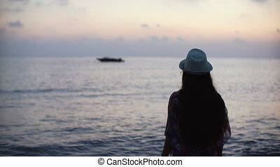 silhouette of young woman with long hair looking forward on sea background at sunset