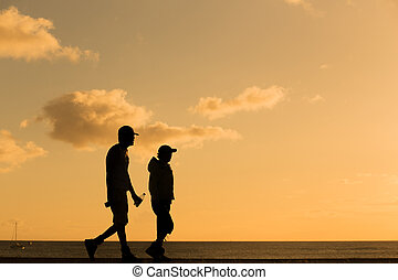 Silhouette people walking at sunset