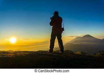 silhouette photographer during sunrise