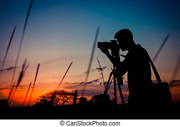 Silhouette photographer with sunset