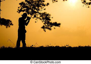 Silhouette photographers take camera landscape